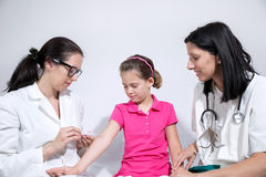 Nurse giving vaccination injection to little girl patient Royalty Free Stock Photo