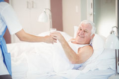 Nurse giving water glass to senior man Stock Photos