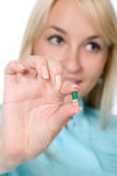Nurse with a green capsule in a hand Royalty Free Stock Photos