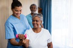 Nurse guiding senior woman in lifting dumbbell Royalty Free Stock Images