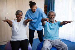 Nurse guiding seniors in exercising. At retirement home Royalty Free Stock Photography