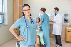 Nurse With Hand On Hip Against Patient And Medical Royalty Free Stock Photography