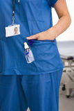 Nurse with hand sanitizer bottle attached to her pocket stock photography