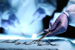 Nurse hand taking surgical instrument. For group of surgeons at background operating patient in surgical theatre. Steel medical instruments ready to be used royalty free stock image