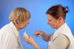 Nurse has measured the temperature of elderly woman Royalty Free Stock Images
