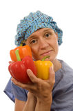 Nurse  healthy diet   bell peppers. Pretty happy and smiling confident nurse promoting healthy diet with fresh colorful bell peppers wearing nurse scrub clothes Royalty Free Stock Image