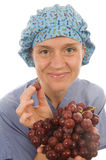 Nurse healthy diet fresh fruit grapes. Pretty happy and smiling confident nurse promoting healthy diet with fresh fruit grapes while wearing nurse scrub clothes Stock Image