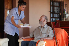 Nurse happy old people care home. Nurse or helper in residential care home giving food to old senior man Royalty Free Stock Photography