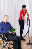 Nurse helping disabled with cleaning Stock Images