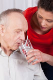 Nurse helping disabled with drinking water Stock Image