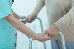 Nurse helping disabled elderly lady Stock Images