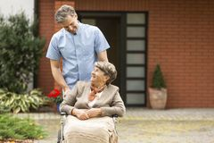Nurse helping disabled happy elderly woman royalty free stock images