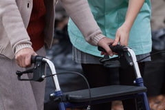 Nurse helping disabled lady with walker Royalty Free Stock Image