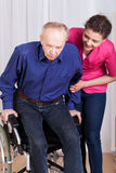 Nurse helping disabled patient. On a wheelchair Stock Photos