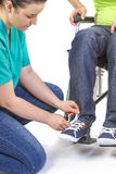 Nurse helping a disabled young man in wheelchair Stock Photos