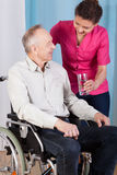 Nurse helping elderly man Stock Photography