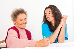 Nurse Helping Elderly Register for Nursing Home Royalty Free Stock Images