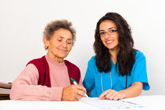 Nurse Helping Elderly Register for Nursing Home Royalty Free Stock Image