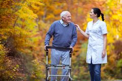 Nurse helping elderly senior man. Senior men using a walker with caregiver outdoor Royalty Free Stock Photos