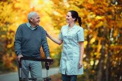 Nurse helping elderly senior man. Senior men using a walker with caregiver outdoor Stock Photos