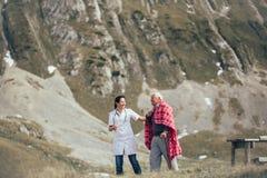 Nurse helping elderly senior man to walk on frash air Stock Photos