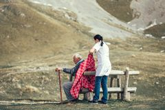 Nurse helping elderly senior man to walk on frash air Royalty Free Stock Images