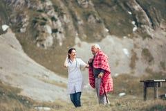 Nurse helping elderly senior man to walk on frash air Stock Photography