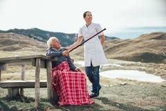 Nurse helping elderly senior man to walk on frash air Royalty Free Stock Photos