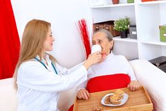 Nurse helping elderly woman Royalty Free Stock Image