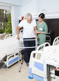 Nurse Helping Male Patient In Using Walker At Rehabilitation Cen Stock Images
