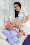 Nurse helping a man in bed to drink water Royalty Free Stock Photos