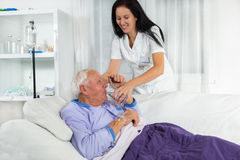 Nurse helping a man in bed to drink water Stock Photography
