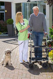 Nurse Helping Man with Walker Take Dog for Walk. Smiling Blond Nurse Holding onto Arm of Senior Man, Helping Man with Walker Walk Dog on Leash Outdoors in front Stock Photo