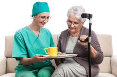 Nurse helping old disabled woman Stock Image