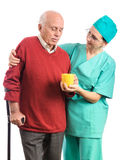 Nurse helping old man cup of tea or pills Stock Photography