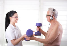 Nurse helping old man with dumbbells Royalty Free Stock Photo