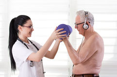 Nurse helping old man with dumbbells Stock Photos