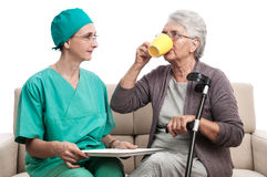 Nurse helping old woman cup of tea at home Royalty Free Stock Photography
