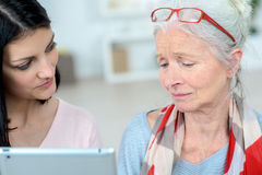 Nurse helping old woman managing daily tasks. Nurse is helping old women managing her daily tasks Royalty Free Stock Photography