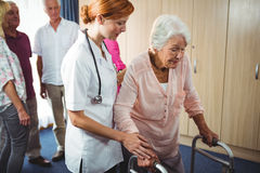 Nurse helping a retired woman to walk. Nurse helping a retired women to walk in a retirement home Stock Images