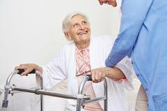 Nurse helping senior citizen. Patient in nursing home getting up stock photos