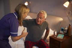 Nurse Helping Senior Man Out Of Bed On Home Visit stock photo