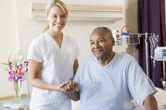 Nurse Helping Senior Man To Walk. On Hospital Ward royalty free stock photography