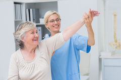 Nurse helping senior patient in exercising Royalty Free Stock Photo