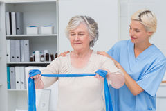 Nurse helping senior patient in exercising with resistance band. In clinic Royalty Free Stock Photography