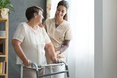 Nurse helping senior to walk. Smiling nurse helping senior lady to walk around the nursing home Stock Photo