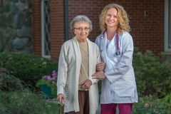 Nurse Helping Senior Walking with Cane Outdoor Royalty Free Stock Photography