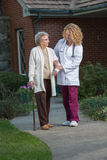 Nurse Helping Senior Walking with Cane Outdoor Royalty Free Stock Photo