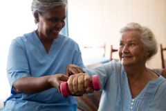 Nurse helping senior woman in lifting dumbell Stock Photos