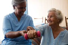 Nurse helping senior woman in lifting dumbell Stock Photo